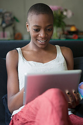 Young woman using digital tablet at home - p301m961096f by Halfdark