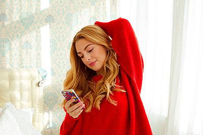 Junge Frau mit Handy im Schlafzimmer - p432m1502391 von mia takahara