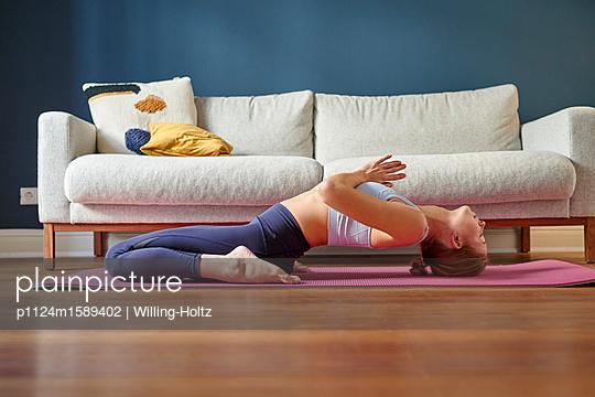Junge Frau macht eine Yoga Übung - p1124m1589402 von Willing-Holtz