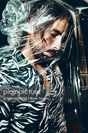 Man wrapped in transparent plastic foil - p1540m2289798 by Marie Tercafs