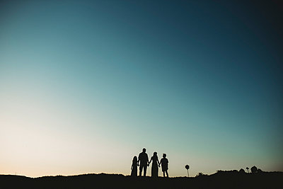 Silhouette of family against teal sky - p1166m2207846 by Cavan Images