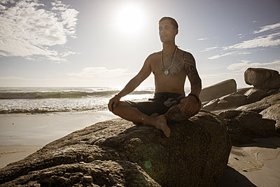 Mann meditiert auf dem Strand im Sonnenschein - p1640m2261015 von Holly & John