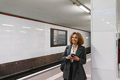 Smiling woman with cell phone waiting in subway station - p300m2143445 by Hernandez and Sorokina