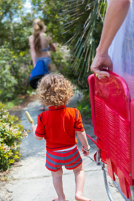 Caucasian family carrying deck chairs to beach - p555m1412243 by Marc Romanelli