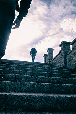 Man walking up steps being followed by other man - p597m1488669 by Tim Robinson