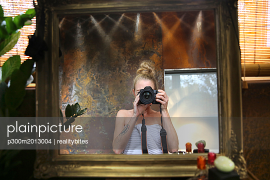Mirror image of woman taking selfie with camera in bathroom - p300m2013004 von realitybites