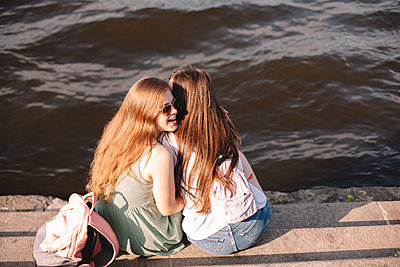 Young woman whispering into her girlfriend‰Ûªs ear sitting by river - p1166m2212427 by Cavan Images