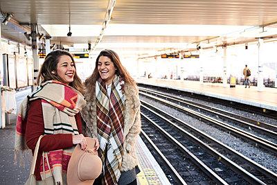 UK, London, two happy women at underground station platform - p300m2103810 by Ivan Gener