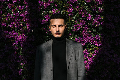 Fashionable man standing with eyes closed against flowering plant wall - p300m2251092 by Ezequiel Giménez