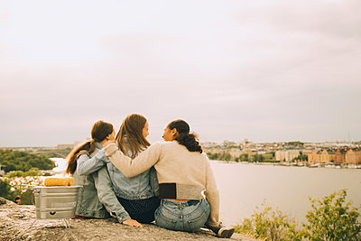 Rear view of female friends relaxing on rock formation at lakeshore against sky - p426m2159295 by Maskot