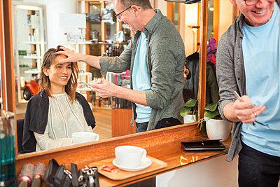 Male hairdresser advising female customer in hair salon - p429m1407776 by Nancy Honey