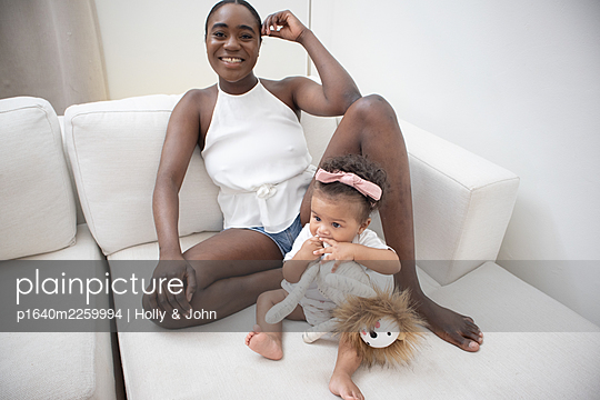 Mother and daughter with cuddly toy on the sofa - p1640m2259994 by Holly & John
