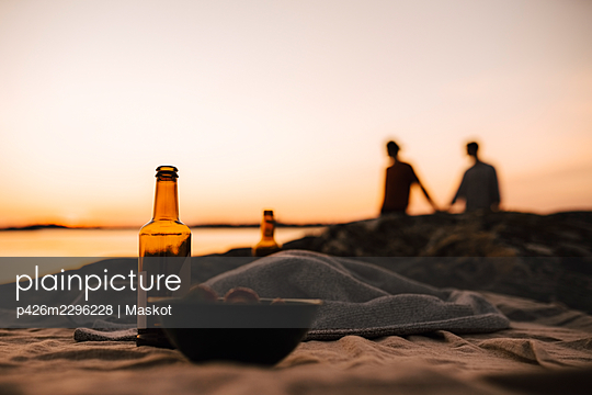 Beer bottle and bowl on picnic blanket while gay couple in background at lakeshore during sunset - p426m2296228 by Maskot