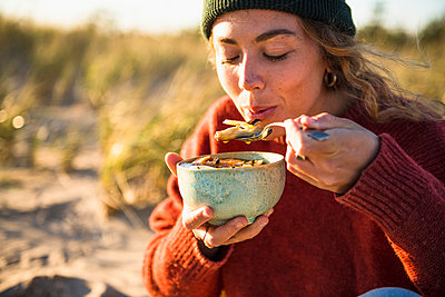 Young woman enjoying soup while beach car camping alone - p1166m2285574 by Cavan Images