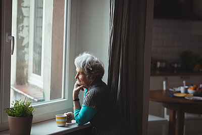 Senior woman looking through window while having coffee at home - p1315m1566645 by Wavebreak