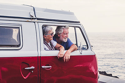 Senior couple traveling in a vintage van, looking at the sea - p300m2114888 by Simona Pilolla