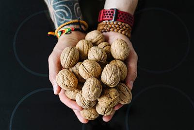 Man holding walnuts over electric stove burner - p300m2287348 by Ekaterina Yakunina