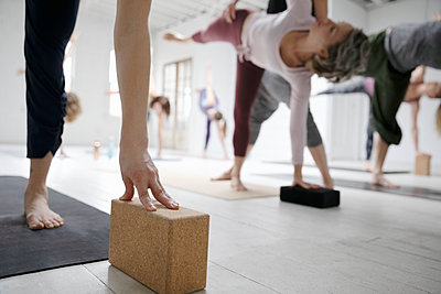 Women practicing half moon pose with blocks in yoga class - p1192m1583399 by Hero Images