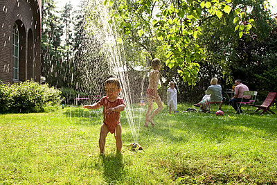Children playing under the sprinkler - p1231m1059787 by Iris Loonen