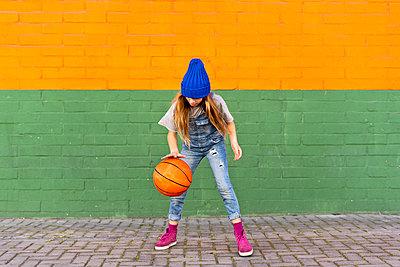 Young girl playing basketball, dribbling - p300m2102965 von Eloisa Ramos