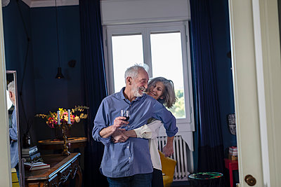 Playful senior couple doing romance while standing at home - p300m2266021 by Emma Innocenti