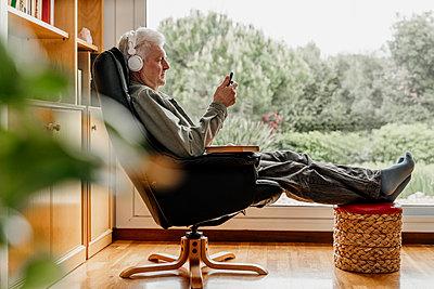 Senior man using smart phone while listening music through headphones at home - p300m2281379 by VITTA GALLERY