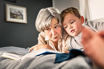Grandmother reading book by grandson in bedroom at home - p300m2287557 by Stefanie Aumiller