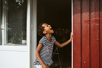 Laughing girl is front of house - p312m2162198 by Stina Gränfors