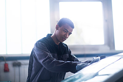 Workman fixing car windshield in workshop - p924m2165384 by Sigrid Gombert