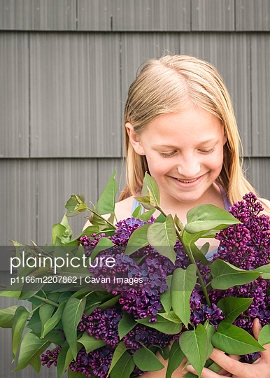 Mid-level view of young girl holding purple flowers and smiling - p1166m2207862 by Cavan Images