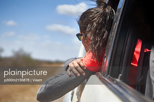 Woman admiring the landscape with the head out of the car window, Kruger National Park, South Africa - p300m2155878 by Veam