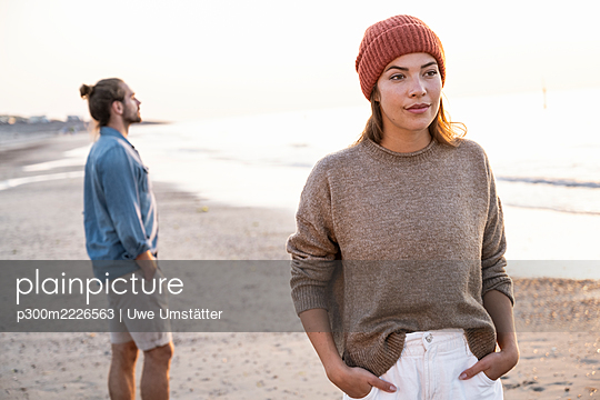 Beautiful young woman standing with hands in pockets against boyfriend at beach during sunset - p300m2226563 by Uwe Umstätter