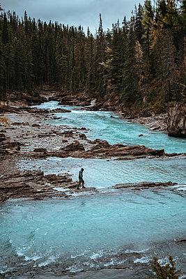 Mann steht auf Steinwand entlang eines Flusses - p1455m2203777 von Ingmar Wein