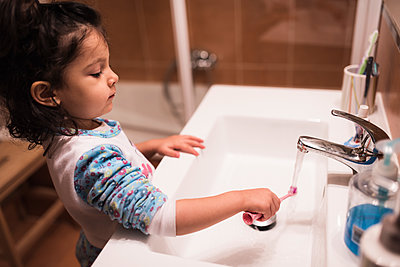Little girl standing in the bathroom going to brush her teeth - p300m1120571f by Jaen Stock