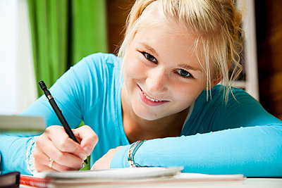 Happy girl studying at home - p4265750f by Tuomas Marttila