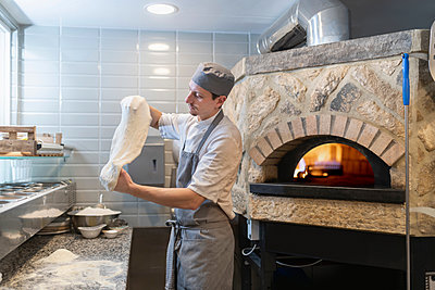 Chef tossing and stretching the dough for Pinsa Romana, a Roman style pizza blend reducing sugar and saturated fat, containing rice and soy with less gluten - p429m2078541 by Monty Rakusen