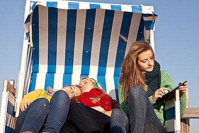 Three girls in a hooded beach chair - p981m952213 by Franke + Mans
