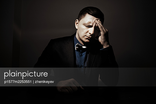 Exhausted man sitting at the table and having headache - p1577m2253551 by zhenikeyev