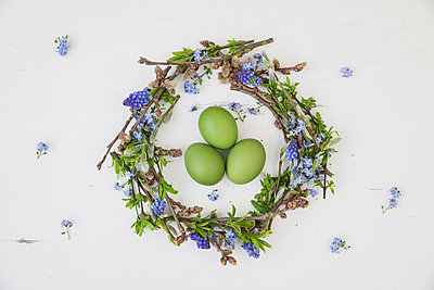 Self-made Easter wreath and green dyed eggs on white ground - p300m2070575 von Gaby Wojciech