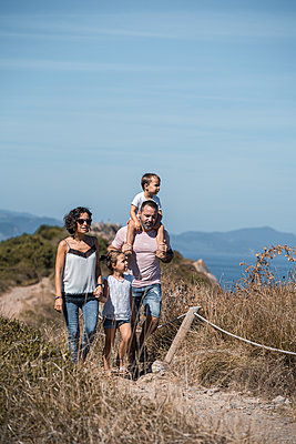 Family hiking at trail against blue sky - p300m2256624 by SERGIO NIEVAS