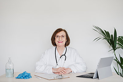 Senior female doctor sitting in front of white wall at desk - p300m2274478 by Eva Blanco