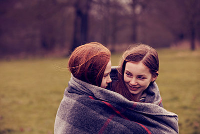 Girls wrapped in a blanket outdoors, smiling - p429m802958f by Emma Kim