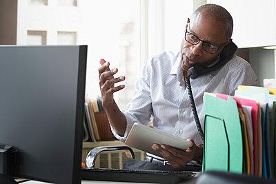 Businessman talking on phone in office - p555m1311438 by Jose Luis Pelaez Inc