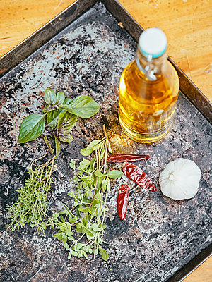 Oil and herbs on baking sheet - p962m2175392 by Robert Schlossnickel