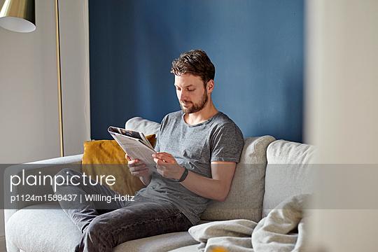 Junger Mann liest eine Tageszeitung - p1124m1589437 von Willing-Holtz