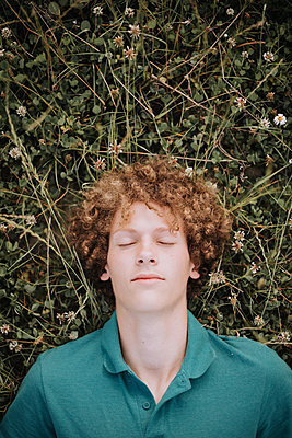 Young man lying on meadow, portrait - p1267m2259724 by Jörg Meier