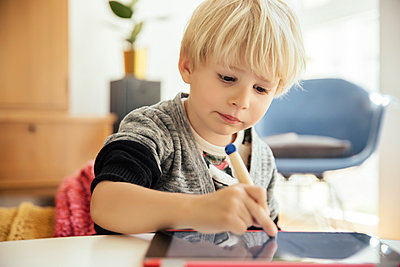 Portrait of little boy drawing with a digital pen on digital tablet at home - p300m1028806f by Mareen Fischinger