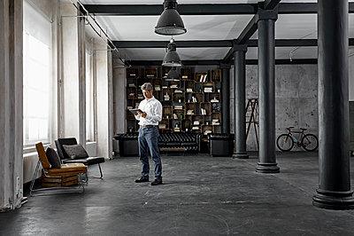 Mature man using digital tablet in loft flat - p300m1581605 von Philipp Dimitri