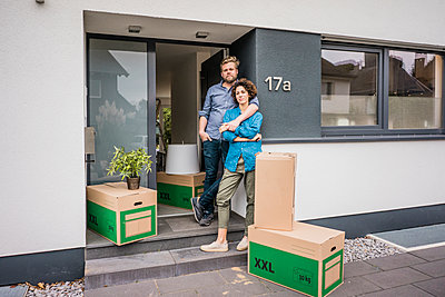 Couple standing at house entrance with cardboard boxes - p300m2080336 by Joseffson