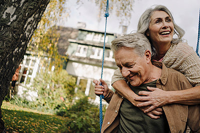 Happy woman embracing senior man on a swing in garden - p300m2155006 by Gustafsson